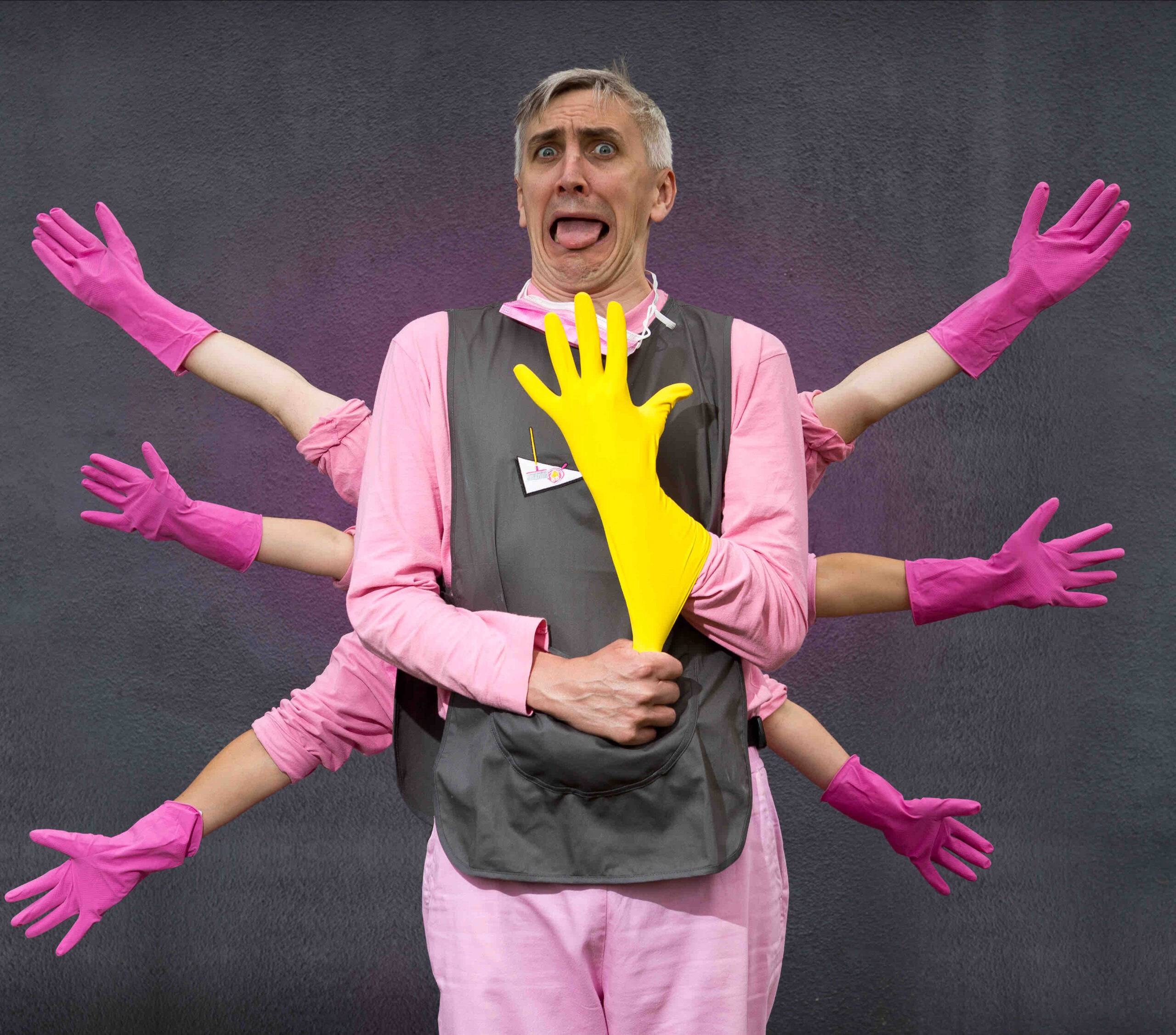 The Chief is standing against the grey painted wall and is wearing a pink t shirt and trousers with a grey tabard over the top. He is pulling a yellow rubber glove onto his hand in front of his body, and his face seems like a mixture of surprise and disgust. Behind him, the other characters' arms fan out on either side. They are all wearing pink rubber gloves.
