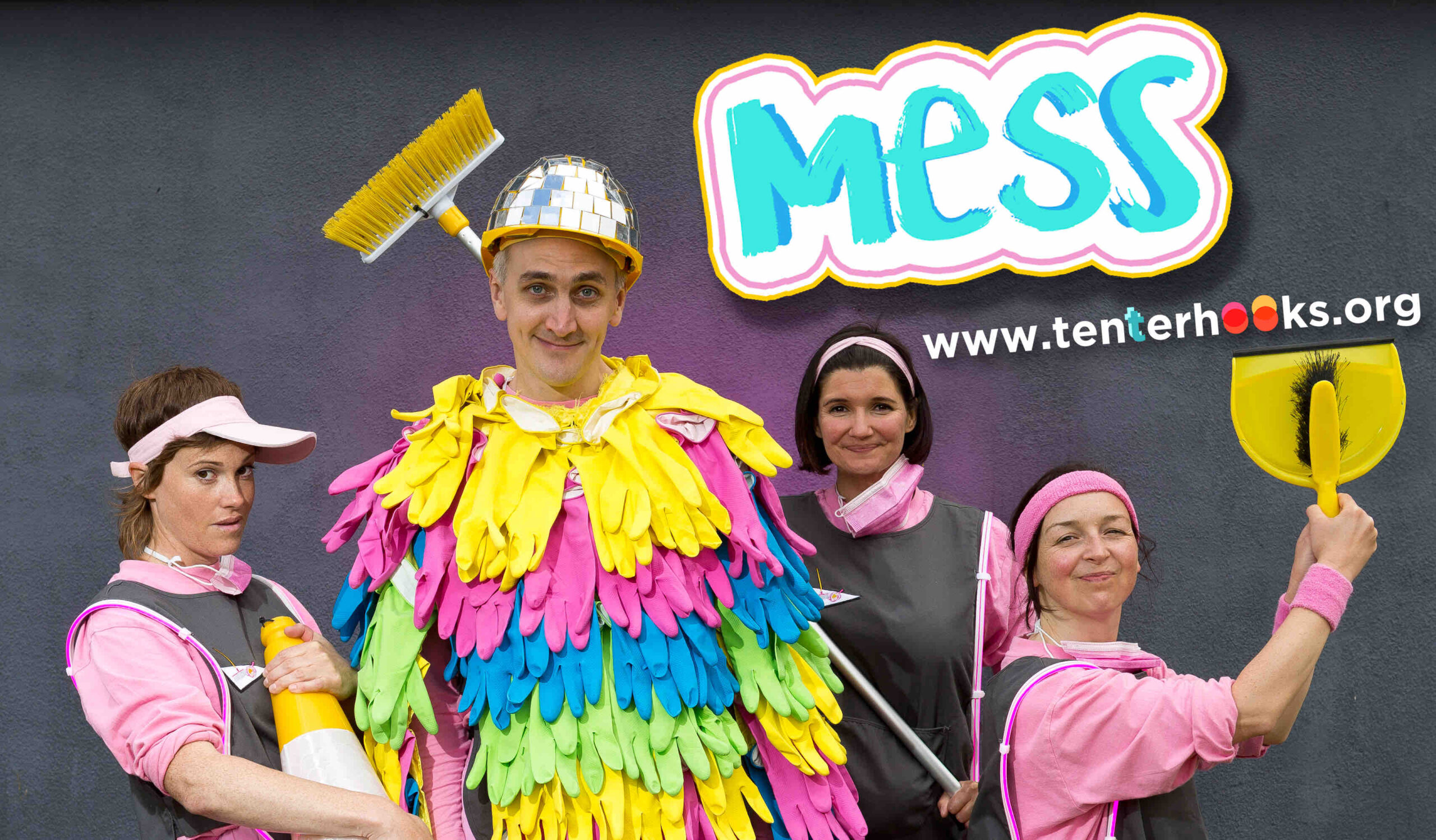 Four caretakers pose with their cleaning implements in front of a painted grey wall as if they are in a rock band. Three of caretakers are wearing a matching light pink uniform with a grey tabard over the top and they are posed around the 'Chief' in the middle of the frame who is wearing a yellow hard hat covered in square mirrors and a poncho made of different coloured rubber gloves - green, pink, yellow and blue. The caretaker on the right is carrying a large yellow traffic cone, to the left of the 'Chief' the caretaker is holding a broom with yellow bristles, and to the right of them, the caretaker is presenting a dustpan and brush out to the side. The 'Mess' logo is to the left at the top of the page, and the Tenterhooks website is written underneath, www.tenterhooks.org