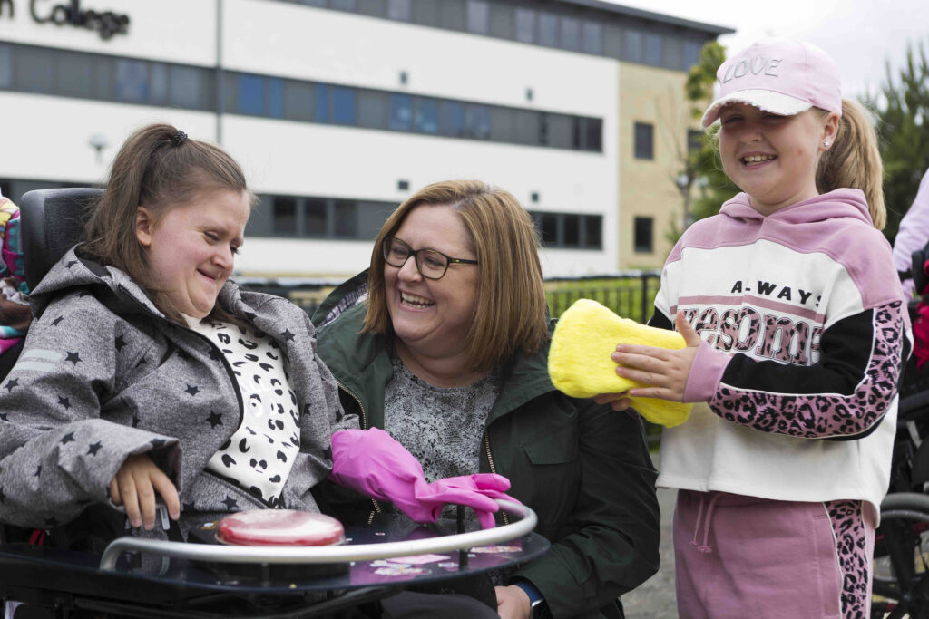 A girl sitting in a wheelchair has a big mac button on her table, and a pink glove on her hand. She appears to be smiling. Her mum is kneeling beside her and looking in her direction and seems to be laughing. Her sister is standing next to her mum, holding a big yellow sponge, and is smiling.