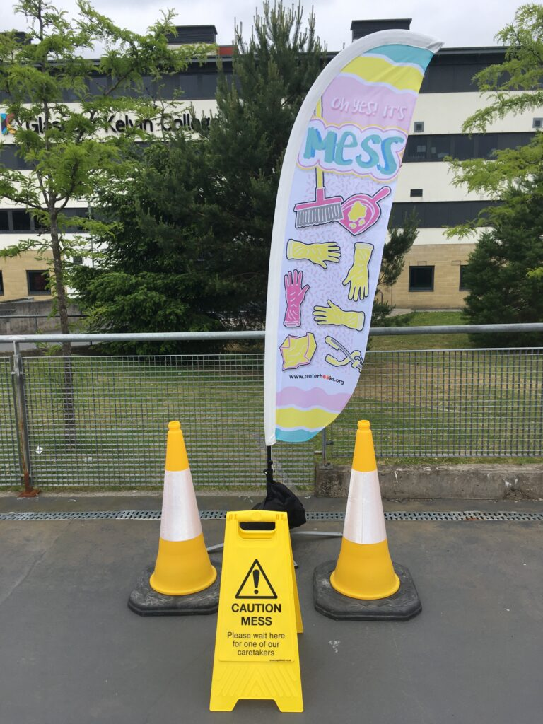A long white vertical flag is standing up between 2 yellow traffic cones and behind a yellow sign that says, 'CAUTION! MESS! Please wait here for one of our caretakers'. The flag is decorated with pictures of props from the show - a dustpan and brush, rubber gloves, a litter picker and a duster, all in pink and yellow pastel colours. At the top of the flag it says 'Oh Yes! It's MESS' and at the bottom of the flag, it has www.tenterhooks.org